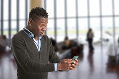 Junger afrikanischer Kerl, der Handy betrachtet Stockbilder