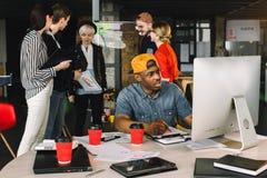 Junger afrikanischer männlicher Architekt in zufälliger Ausstattung Funktion am Schreibtisch auf Computer Kreative Kollegen, die  lizenzfreie stockfotografie