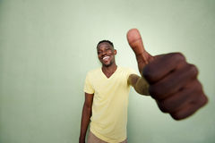 Junger afrikanischer Mann, der Daumen herauf Zeichen durch grüne Wand gestikuliert Lizenzfreies Stockbild