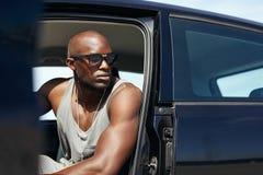 Junger afrikanischer Mann, der im Auto weg schaut sitzt Stockbilder