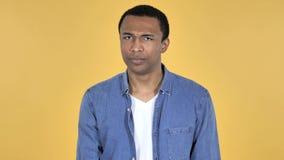 Junger afrikanischer Mann, der Kopf rüttelt, um zurückzuweisen, gelber Hintergrund stock video footage