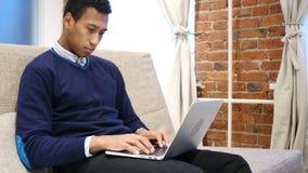 Junger afrikanischer Mann, der an Laptop nachts arbeitet stock video