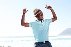 Junger afrikanischer Mann, der Spaß am Strand hat Lizenzfreies Stockfoto