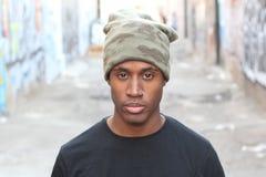 Junger afrikanischer Mann mit Durchdringen und Beanie draußen stockbild
