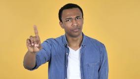 Junger afrikanischer Mann-wellenartig bewegender Finger zum abzulehnen, gelber Hintergrund stock video footage