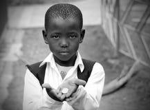 Junger afrikanischer Schule-Junge, der um Geld bittet Stockbild
