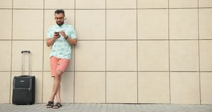 Junger afrikanischer Tourist ist zu einem Flug bereit Er hört Musik und plaudert glücklich am Handy während stock video