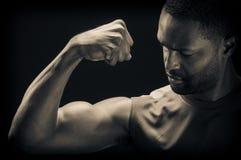 Junger Afroamerikaner-Mann, der Bizeps biegt Stockbilder