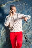 Junger Afroamerikaner-Mann, der am Handy, wri betrachtend spricht lizenzfreie stockfotografie