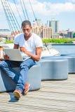Junger Afroamerikaner-Mann, der in New York, arbeitend an Schoss reist Stockbilder