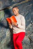 Junger Afroamerikaner-Mann, der rotes Buch am Park in New York liest lizenzfreie stockfotos