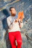 Junger Afroamerikaner-Mann, der rotes Buch am Park in New York liest stockfotos