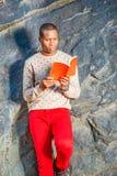 Junger Afroamerikaner-Mann, der rotes Buch am Park in New York liest lizenzfreies stockbild