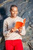 Junger Afroamerikaner-Mann, der rotes Buch am Park in New York liest lizenzfreies stockfoto