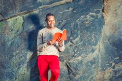 Junger Afroamerikaner-Mann, der rotes Buch am Park in New York liest stockbild