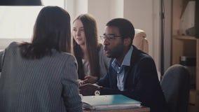 Junger Afroamerikanerangestellter hört auf unerkennbaren weiblichen Führer an der modernen BüroGeschäftstreffenzeitlupe stock video footage