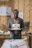 junger Afroamerikanerarchitekt mit Papierhausmodell lizenzfreie stockfotografie
