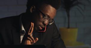 Junger AfroamerikanerB?roangestellter, der am Telefon mit dem Chef, sp?t sitzend im modernen B?ro nachts spricht und schwer arbei stock video
