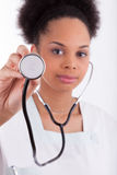 Junger Afroamerikanerdoktor mit einem Stethoskop. stockfotos