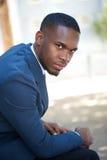 Junger Afroamerikanergeschäftsmann, der draußen sitzt Stockfotos