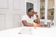 Junger Afroamerikanergesch?ftsmann, der an einem Laptop in der K?che in einem modernen Innenraum arbeitet stockbilder