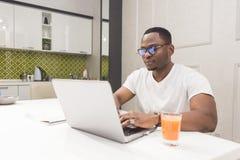 Junger Afroamerikanergesch?ftsmann, der an einem Laptop in der K?che in einem modernen Innenraum arbeitet lizenzfreie stockfotos