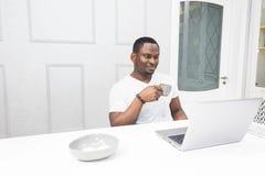 Junger Afroamerikanergesch?ftsmann, der an einem Laptop in der K?che in einem modernen Innenraum arbeitet stockfoto
