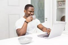 Junger Afroamerikanergesch?ftsmann, der an einem Laptop in der K?che in einem modernen Innenraum arbeitet stockbild