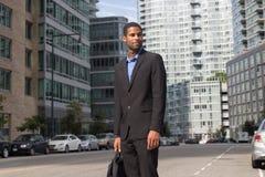 Junger Afroamerikanermann, der auf der Straße, schauend zum Th steht Lizenzfreie Stockfotos