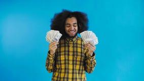 Junger Afroamerikanermann, der Bargeld auf blauem Hintergrund h?lt stock video footage