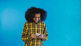 Junger Afroamerikanermann, der Bargeld auf blauem Hintergrund z?hlt stock video footage