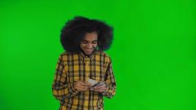 Junger Afroamerikanermann, der Bargeld auf grünem Schirm oder Farbenreinheitsschlüsselhintergrund zählt stock video footage