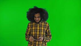 Junger Afroamerikanermann, der Bargeld auf gr?nem Schirm oder Farbenreinheitsschl?sselhintergrund z?hlt stock video footage