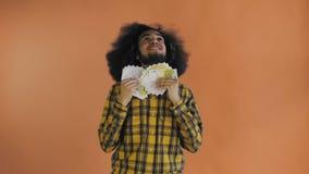 Junger Afroamerikanermann, der Bargeld auf orange Hintergrund hält stock video