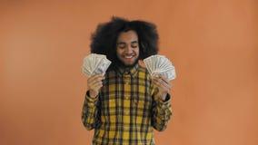 Junger Afroamerikanermann, der Bargeld auf orange Hintergrund h?lt stock video footage