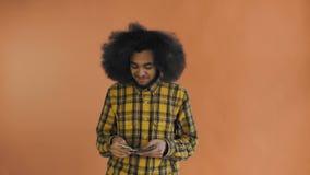 Junger Afroamerikanermann, der Bargeld auf orange Hintergrund zählt stock video footage