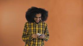 Junger Afroamerikanermann, der Bargeld auf orange Hintergrund z?hlt stock video