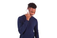 Junger Afroamerikanermann, der einen Telefonanruf auf ihrem Smartphone macht stockfotos