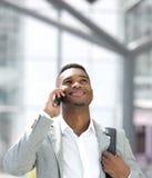 Junger Afroamerikanermann, der mit Handy lächelt Lizenzfreie Stockfotografie