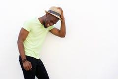 Junger Afroamerikanermann, der mit Hut gegen weißen Hintergrund lächelt Stockbilder