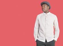 Junger Afroamerikanermann, der seitlich über rotem Hintergrund schaut lizenzfreies stockfoto