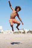 Junger Afroamerikanermann, der am Strand springt Lizenzfreie Stockfotos