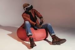 junger Afroamerikanermann im Kopfhörer der virtuellen Realität, der mit Steuerknüppel beim Sitzen auf Bohnentaschenstuhl spielt lizenzfreie stockfotografie
