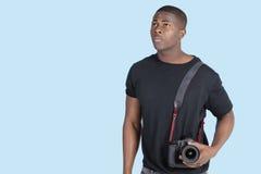 Junger Afroamerikanermann mit der Digitalkamera, die oben über blauem Hintergrund schaut Lizenzfreie Stockbilder