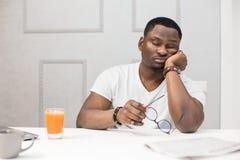 Junger Afroamerikanermann schläft am Frühstück in der Küche ein lizenzfreie stockbilder