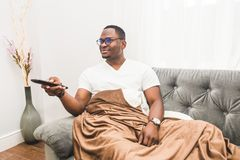 Junger Afroamerikanermann, zu Hause bedeckt mit einer Decke, aufpassendes Fernsehen stockfoto