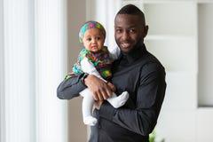 Junger Afroamerikanervater, der mit ihrem Baby hält Stockbild