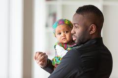Junger Afroamerikanervater, der mit ihrem netten Baby hält Lizenzfreie Stockfotos