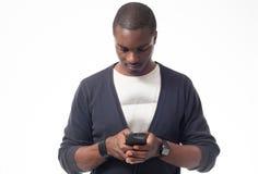 Junger afroer-amerikanisch Mann, der seinen Handy schaut Lizenzfreie Stockfotografie