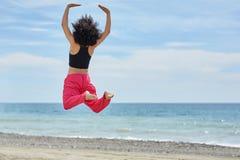 Junger afroer-amerikanisch Tänzer, der auf Strand springt Stockbild